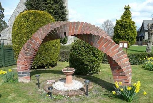 Декоративная садовая арка подчеркивает необычность всей композиции