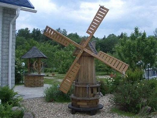 Ветряная деревянная мельница украшает садовую композицию